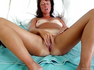 Tanlined mature woman orgasms while masturbating in bed all alone