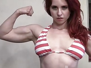 Muscular redhead showing off her muscles