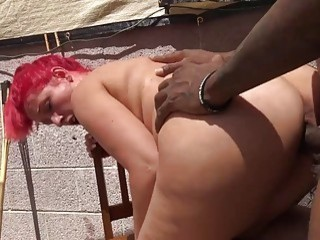 Redhead moans in pleasure while sucking a big black cock
