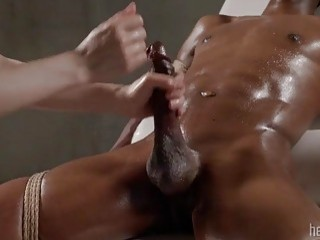 Tied-up black dude gets his dick massaged and slapped